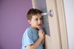 Gridando, bambino spaventato che ascolta un genitore che parla attraverso la porta fotografia stock