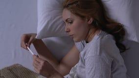 Gridando femmina a letto che tiene test di gravidanza con il risultato negativo, sterilità archivi video