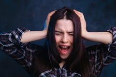Gridando, giovane donna di grido, soffrente dall'emicrania, studio fotografia stock libera da diritti