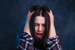 Gridando, giovane donna spaventata e di grido, soffrente dall'emicrania immagine stock