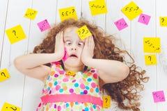 Gridare bambino con il simbolo di domanda con gli autoadesivi sulla sua testa e Fotografie Stock Libere da Diritti