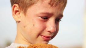 Gridare del primo piano del ragazzo e coccole orfane sporche a stock footage