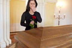 Gridare donna con la rosa rossa e la bara al funerale fotografie stock
