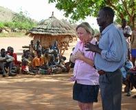 Gridare emozionale del volontario di sollievo dell'aiuto di fronte al villaggio Africa di povertà immagine stock