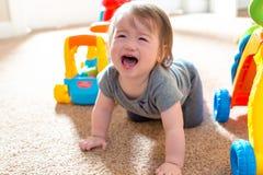 Gridare il ragazzo del bambino che gioca con i suoi giocattoli fotografia stock