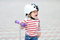 Gridare il ragazzo del bambino nel casco di sicurezza con il motorino immagine stock libera da diritti