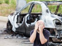Gridare l'uomo turbato al fuoco di incendio doloso ha bruciato il ciarpame del veicolo dell'automobile Fotografie Stock