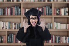 Gridare laureato della femmina emozionante alla biblioteca Fotografie Stock