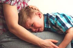 Gridare ragazzo infelice che abbraccia sua madre Fotografia Stock