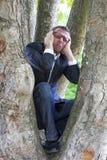 Gridare uomo d'affari che scala in un albero per protezione della madre Terra Immagini Stock