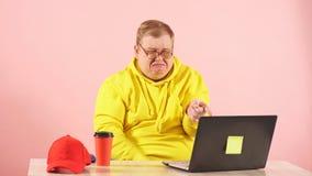 Gridare uomo in maglia con cappuccio gialla che guarda film triste su laptot e che indica allo schermo video d archivio