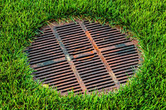 Gridded Abwasserkanaleinsteigeloch auf grünem Rasen Lizenzfreies Stockbild