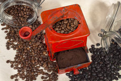 Gridding coffee with a red manual coffee grinder Royalty Free Stock Photo