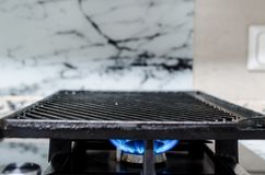 Griddle on a gas stove. Cast iron griddle sitting on a gas fired stove top Royalty Free Stock Image