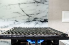 Griddle on a gas stove. Cast iron griddle sitting on a gas fired stove top Stock Image