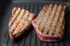 Griddled Steaks. Seasoned steaks being seared in a hot skillet pan Royalty Free Stock Photo