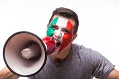 Gridi sul tifoso italiano del megafono nell'appoggio del gioco della squadra nazionale dell'Italia su fondo bianco fotografie stock