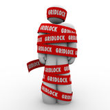 Gridlock Man Wrapped in Tape Immobile Person Bureaucracy Stoppag. Gridlock red tape wraped around a man or person who is trapped, stopped or prisoner to a Stock Images