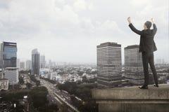 Grido dell'uomo di affari sul tetto della costruzione Fotografie Stock