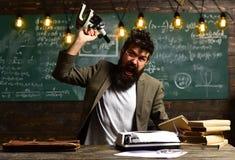 Grido sollecitato dell'uomo d'affari con il microscopio Uomo con la barba e baffi sul fronte arrabbiato Uomo con il libro e retro Immagine Stock