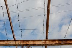 Gridwork of overhead beams, painted and rusted, against a blue sky royalty free stock photo