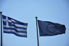 Grieche und EU-Flaggen, die zusammen nebeneinander fliegen Lizenzfreie Stockfotos