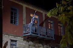 Griechenland-Flagge senkte außerhalb eines Blau gemalten hölzernen Balkons lizenzfreies stockfoto