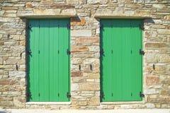 Griechenland, grüne Türen des Doppelten auf Steinwand Lizenzfreie Stockbilder