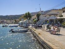 Griechenland, Korfu, Kassiopi am 28. September 2018: Tourist mit zwei älterer Leutepaaren, der an auf Bank auf Quay mit Ansicht s lizenzfreie stockfotografie
