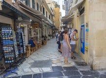 Griechenland, Korfu, Kerkyra-Stadt, am 26. September 2018: Alte Stadthauptstraße Korfus mit dem älteren Mann, der heraus etwas Ba lizenzfreie stockfotografie