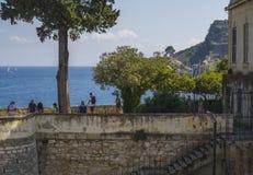 Griechenland, Korfu, Kerkyra-Stadt, am 26. September 2018: Touristische Leute auf Steinwandpromenade mit grünen Bäumen und Ansich lizenzfreies stockbild