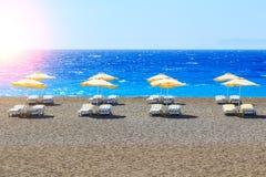Griechenland, Reedregenschirme und gelbe sunbeds auf Pebble Beach in Ägäischem Meer von Rhodos, Stockbild
