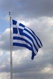 Griechische Flagge auf einem Fahnenmast gegen dunkle Wolken stockbild