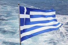 Griechische Flagge, die mit Meereswellen im Hintergrund flattert Stockbild