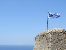 Griechische Flagge im Hintergrund des reinen blauen Himmels und des Meeres Lizenzfreie Stockbilder
