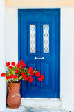 Griechische Haustür herein mit Pelargonienblumen Stockbild