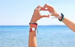 Griechische Schmuckanzeige auf dem Strand - Herzsymbol mit den Händen Stockbilder