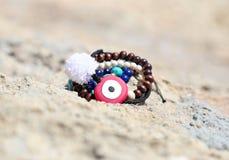 Griechische Schmuckanzeige auf dem Strand mit bösem Blick und halb Edelsteinen Stockfotos