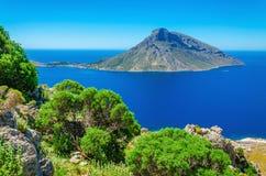 Griechische Vulkan Insel mit grünen Büschen, Griechenland Lizenzfreie Stockfotos