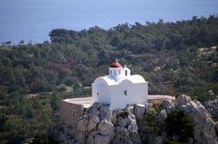 Griechische weiße Kapelle auf einem Hügel Stockfotografie