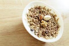Griechischer Artjoghurt des gesunden Frühstücks mit Granola in einer weißen Schüssel auf einem Holztisch Stockfotos