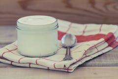 Griechischer Jogurt auf einem Weinleseholzhintergrund lizenzfreie stockfotos