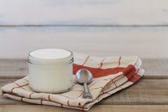 Griechischer Jogurt auf einem Weinleseholzhintergrund lizenzfreie stockbilder