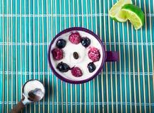 Griechischer Jogurt mit Blaubeeren und Himbeeren mit Zitrone oder Zitrusfrucht auf einer rustikalen weichen blauen Hintergrundsom Lizenzfreie Stockbilder