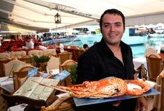 Griechischer Kellner mit Hummer Stockfotografie