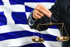 Griechischer Richter hält goldene Skalen von Gerechtigkeit mit wellenartig bewegendem Flaggenhintergrund Griechenlands Gleichheit stockbilder