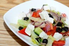 Griechischer Salat auf weißer Platte, Nahaufnahme Stockfotos