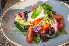 Griechischer Salat in der Platte in den Sonnenstrahlen Stockfotos