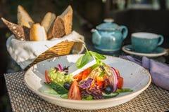 Griechischer Salat in der Platte in den Sonnenstrahlen Lizenzfreie Stockfotos