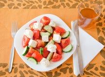 Griechischer Salat diente auf einer gelben Tischdecke. Lizenzfreies Stockbild